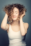 Young smiling woman holding her curly hair up. - 173748156