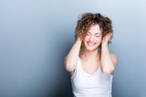 Young, smiling woman holding her curly hair up. - 173748374