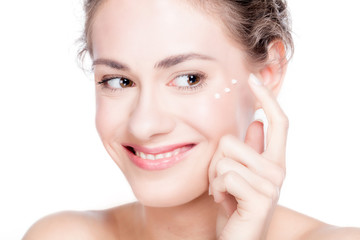 Beautiful young woman smiling and putting eye cream. © Photocreo Bednarek