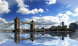 Tower Bridge spanning the River Thames with a dramatic blue cloudy sky and good water reflection