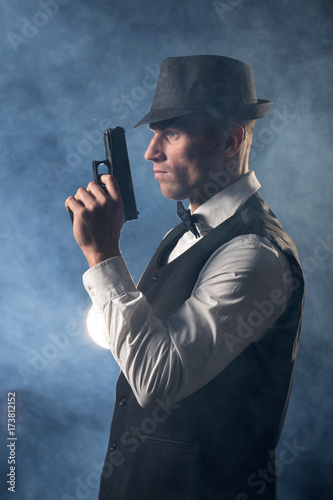 Poster detective or criminal with gun on foggy night background