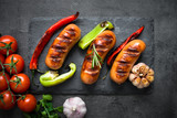 Fried bbq sausages with  vegetables at black background. Top view. - 173815758