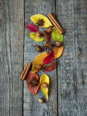 Autumn background with dry leaves, nuts, acorns cinnamon spices on wooden table. Copy space