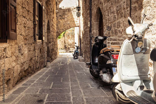 Motorbike scooters are parked near the wall at narrow street of Rhodes town on Rhodes island, Greece