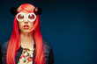 fashion girl with pink hair and big sunglasses over blue  background