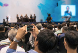 Speakers on the stage with Rear view of Audience taking photo or video for Live in the conference hall or seminar meeting, business and education about investment concept - 173864934