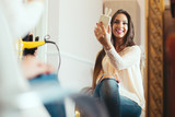 Happy young woman with smartphone taking mirror selfie at hair salon - 173879511