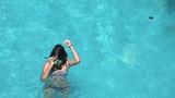 Girl preparation for diving, putting on snorkeling mask - 173897168