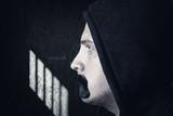 Seitenansicht von einem schweigenden Mann in einer Gefängniszelle, dessen Mund mit einem schwarzen Klebestreifen  - 173927529