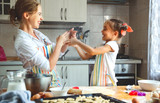Happy family mother and daughter bake kneading dough in kitchen. - 173943977