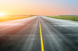 Fototapety Asphalt road with a dividing strip in the horizon at sunset.