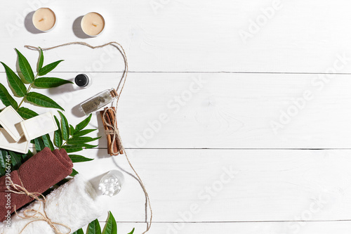Natural handmade soaps with oil, cinnamon, candles, brown towel and green leaves on white wooden background © nazarovsergey