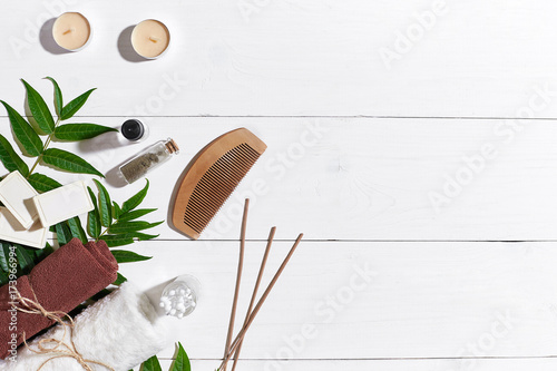Natural handmade soaps with oil, candles, brown towel and green leaves on white wooden background © nazarovsergey