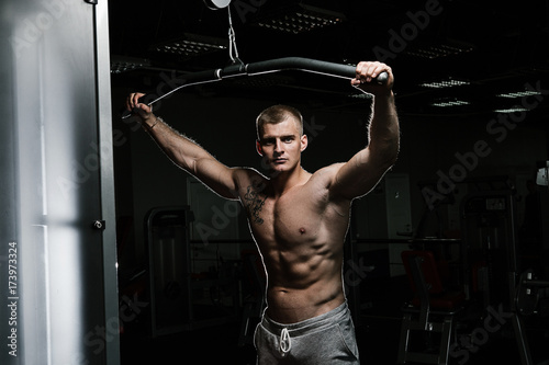Strong man with tatoo working in gym