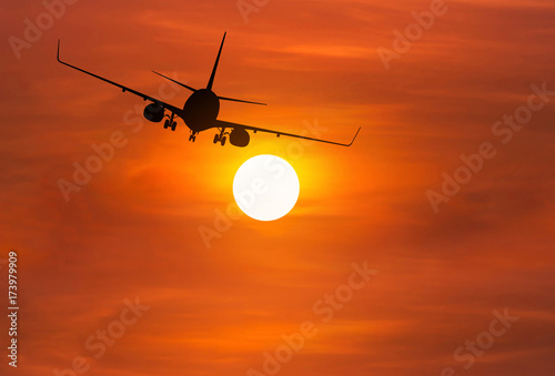 Foto op Canvas Baksteen Silhouette airplane flying away in to sky high altitude above the sun during sunset
