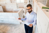 Architect or home owner at the construction site. - 173982175