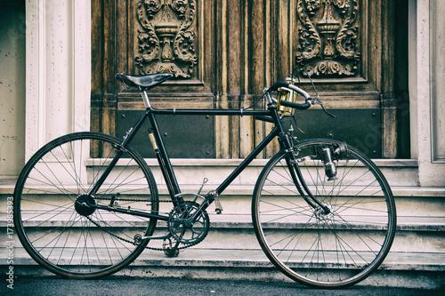 Tuinposter Fiets Una vecchia bicicletta davanti a un vecchio portone