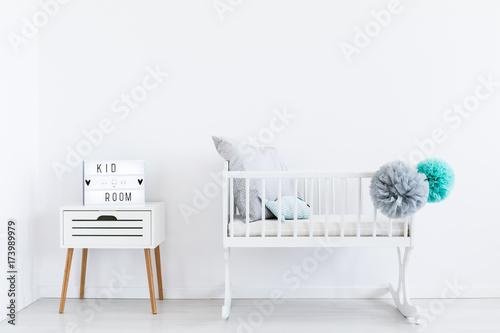 Fototapeta White cradle with pastel pompons