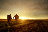 A young couple is traveling with backpacks across the field at sunset. - 173990341