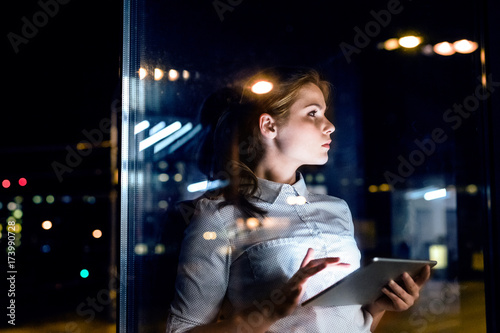 Businesswoman with tablet working late at night.