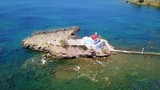 August 2017: Aerial drone video of iconic chapel of Agios Isidoros built in a rock next to the coast with clear turquoise waters, Leros island, Aegean, Dodecanese, Greece - 174007713