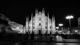 Milan, Italy. Cathedral of Milan, Italy at night - famous landmark in Italy. Motion blurred people, dark sky. Time-lapse. Black and white - 174014397
