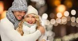 happy couple hugging over christmas lights - 174020791