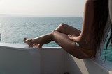 Legs close-up. A girl in a bathing suit sits by the side of the yacht and enjoys the view