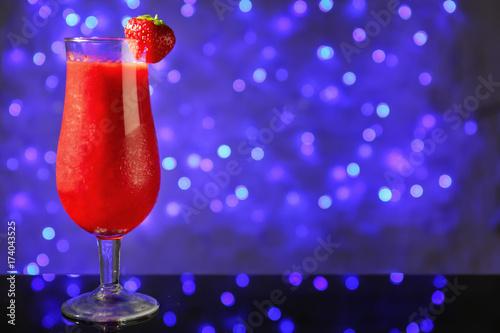 Leinwanddruck Bild Glass of delicious strawberry daiquiri on table against defocused lights