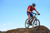 Cyclist in Red Riding the Bike Down the Rock on the Blue Sky Background. Extreme Sport and Enduro Biking Concept. - 174050329