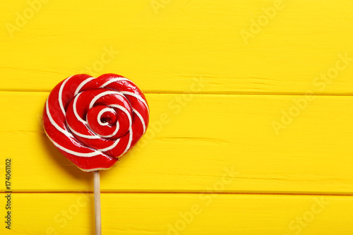 Sweet lollipop on a yellow wooden table Poster