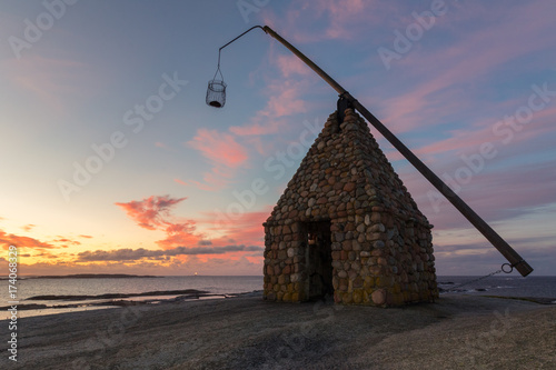 Foto op Aluminium Strand Old lighthouse made of rocks, in beautiful sunrise at Verdens Ende in Vestfold Norway