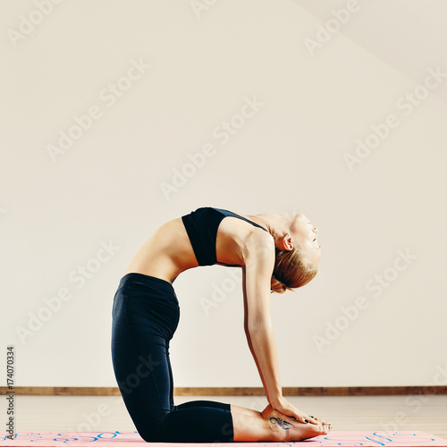 Fotobehang School de yoga Young fit woman doing yoga indoors