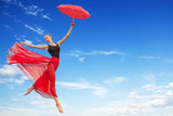 Young Woman Jumping in the Sky with Red Umbrella - 174076990