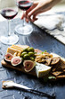 Hand Reaching for Winde Glass Beautiful Date Night Cheese Board with Cheddar Manchego and Blue Cheese Prosciutto Almonds and Olives on Wooden