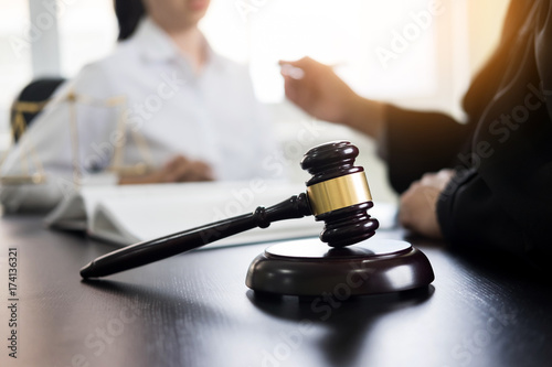 Fototapeta Judge gavel with lawyers advice legal at law firm in background. Concepts of law, services.