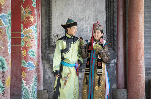 Fototapeta mongolian couple in traditional 13th century style outfit walking near old temple