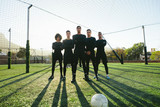 Soccer players standing together on pitch - 174179513
