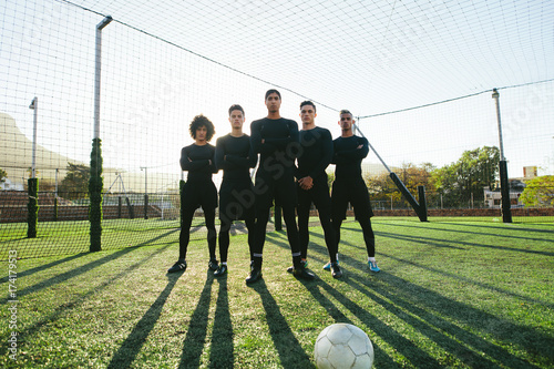 Soccer players standing together on pitch
