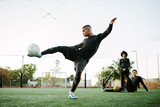 Player kicking soccer ball on field - 174179758