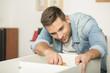 Young man at home assembling furniture parts