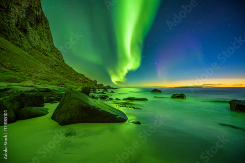 Fotobehang Noorderlicht Beach in the Lofoten islands in Norway with strong green northern lights