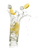 glass full of water with lemon slices and ice cubes falling and splashing water, on white background