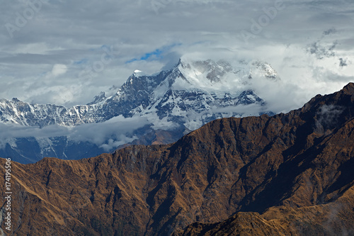 Plagát Mountain peak of Chaukamba among clouds with brown mountain ridge in foreground, the Himalayas, Uttarakhand, India