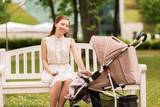happy mother with smartphone and stroller at park - 174196719