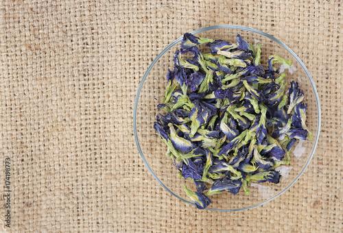 Deurstickers Vlinders in Grunge Dried pea flowers in plate against sack background. Top view.