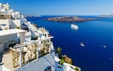 White houses of Fira, Santorini with Santorini's famous volcano and ships in background - 174227711