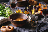 Holiday table decoration setting with bowls of hot soup, baking pumpkin, carrot, garlic, fresh coriander, pretzels bread, red wine, berries over wooden table. Rustic style - 174229934