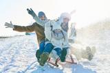 Familie fährt begeistert auf dem Schlitten - 174243594