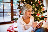 Senior woman in front of Christmas tree - 174252725